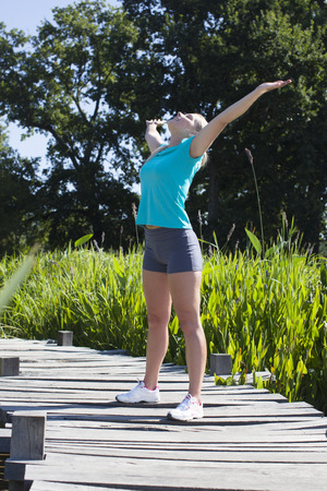 openness: thrilled blond girl enjoying opening her arms wide up for sunny energy, mindfulness, breathing for openness and healthy sports in a beautiful green environment, outdoors