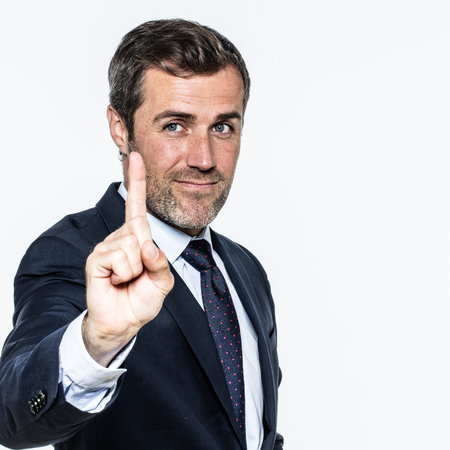 goodlooking: smiling good-looking young business man showing one finger to hold on, listen or wait for time in management or self-confident corporate leadership, isolated, white background