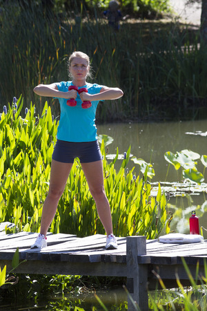 muscle toning: athletic young blond woman training with dumbbells to tone up her arms, exercising on a wooden bridge and water in a beautiful natural park, summer outdoors Stock Photo