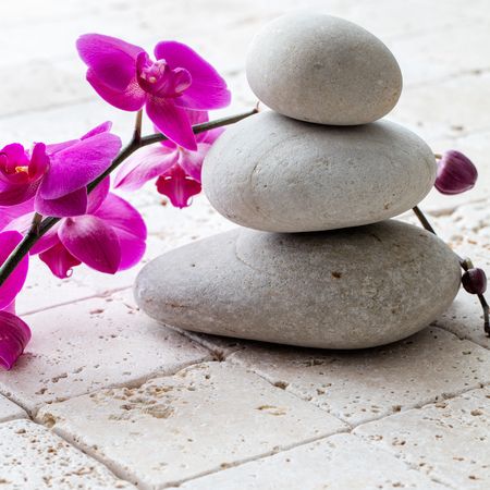 femininity: concept of wellbeing, meditation and femininity with stack of balancing pebbles or stones over beautiful orchids and limestone background