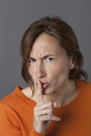 shush: unhappy beautiful middle aged woman requiring silence, discretion or warning for quietness with finger on lips, grey background Stock Photo