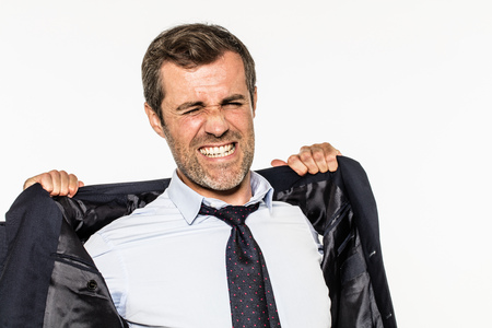 suffocating: angry young bearded businessman grinding teeth for exasperation at work, opening up his suit for corporate suffocation, not breathing from frustration, isolated, white background Stock Photo