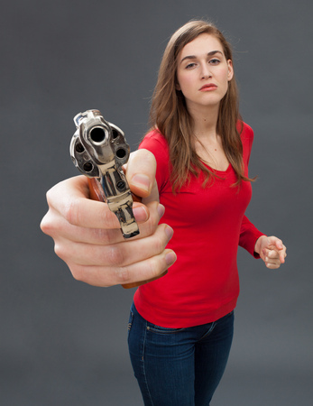 intimidate: beautiful arrogant young woman provoking with an oversized hand gun in the foreground, threatening and accusing with a firearm Stock Photo