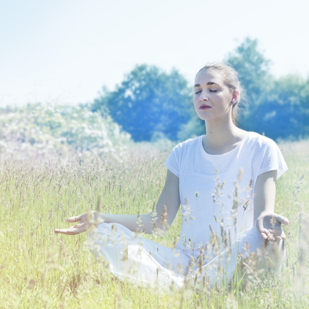 calm beautiful young yoga woman wearing white, closing eyes, sitting crossed-legged in grass in connection to nature and mindfulness, soft vintage toned filter