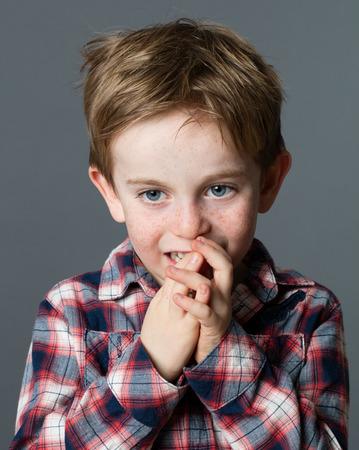 poco: pensando niño pequeño con pecas y pelo rojo morder los dedos para el aburrimiento o nerviosismo, fondo gris Foto de archivo