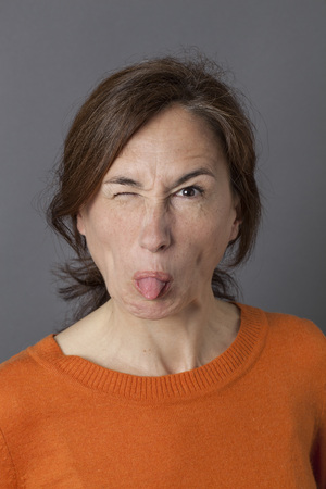 awkward: fun middle aged woman joking, winking and sticking out her tongue for a funny face, playful awkward portrait and humor, grey background