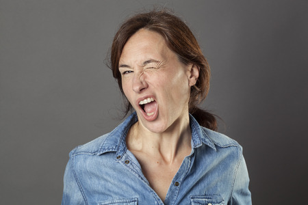 seduction: excited beautiful middle aged woman enjoying winking, making a funny face for cheeky modern seduction, fun natural portrait over grey background