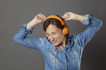 extrovert beautiful middle aged woman with eyes closed enjoying dancing with fashionable headphones on for joyful wellbeing, grey background