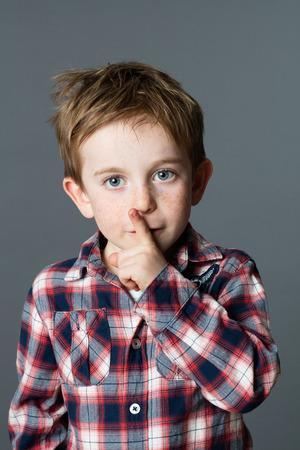 happy 6-year old child with freckles and red hair asking for silence and keeping mystery with his finger on lips, grey background