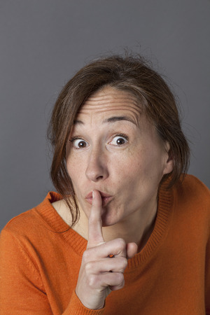 discretion: imaginative beautiful middle aged woman playing with a finger on her lips for sign of fun silence, discretion or mystery with cheerful excitement, grey background