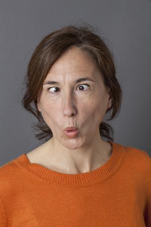 goofy: fun middle aged woman with cross-eyed funny face and pouting mouth for playful and goofy portrait and female humor, grey background