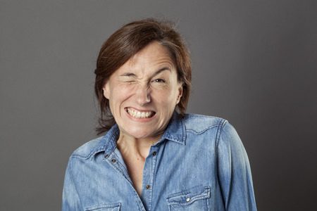 hilarious: hilarious middle aged woman showing her teeth in trying to wink for fun dynamic flirting, humorous portrait over grey background