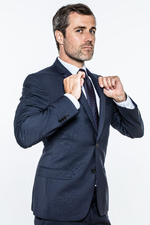 expressing: ambitious young bearded businessman expressing pride, power, success with attitude and superiority with his hands checking his suit, isolated over white background