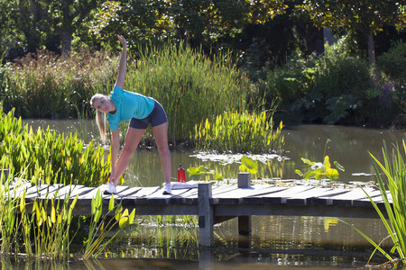 body toning: healthy young blond woman stretching her arms down, exercising on a wooden bridge and water in a beautiful natural park, outdoors