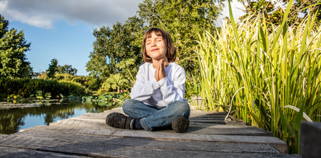 crosslegged: zen young yoga child cross-legged enjoying meditating alone, closing eyes for relaxation and breathing on a wooden bridge near water with blue sky, low angle view