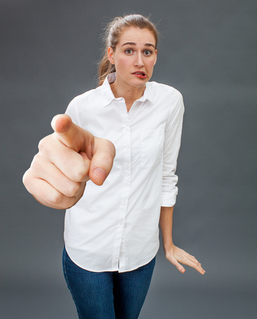 reproach: uncertain beautiful young woman hesitating at pointing her big index to the foreground for concept of stressful defense, accusation or embarrassing reproach, grey background