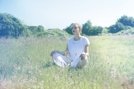 centered: calm beautiful young woman with eyes closed relaxing in green nature, crossing legs for zen yoga and centered mindfulness, soft toned retro effects