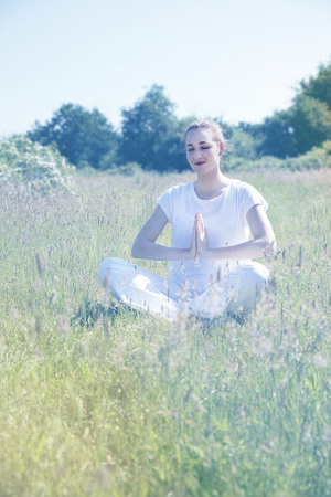 quietness: smiling yoga girl praying cross-legged, relaxing for peaceful retreat, quietness and inner beauty in healthy nature, soft vintage toned filter