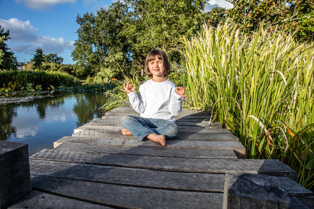 bare feet boys: zen beautiful young 5-year old kid doing yoga bare feet relaxing alone, closing eyes for relaxation and mindfulness on a wooden bridge near water and reed