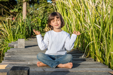 smiling beautiful young 5-year old child doing yoga bare feet cross-legged alone, closing eyes for relaxing energy on a wooden bridge in sunny natural environment Stockfoto
