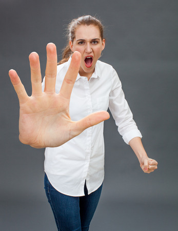 rebellion: furious young woman showing an over sized stopping hand in the foreground for self-defense, anger or rebellion, grey background