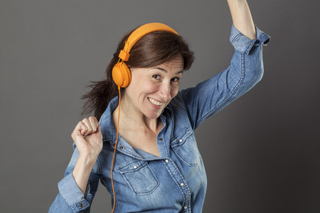 joyous: joyous beautiful middle aged woman dancing in listening to music on fashionable headphones for happiness and fun wellness, grey background