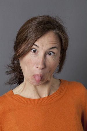 goofy: funny face for happy middle aged woman with eyes wide opened, tongue stuck out the mouth for goofy and playful effects, grey background