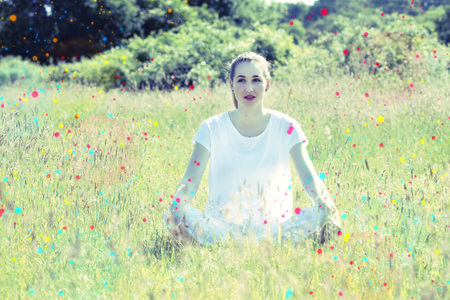 contemplation: daydreaming beautiful young yoga woman sitting on grass with colorful dots around relaxing for pure happiness, energy and contemplation in the countryside, colored toned filter
