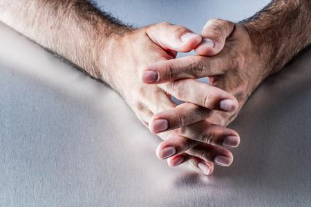 paciencia: peludas manos masculinas anónimos que cruzan los dedos esperando o pensamiento, explicar y comunicar acerca de la moderación o la paciencia en el lenguaje corporal
