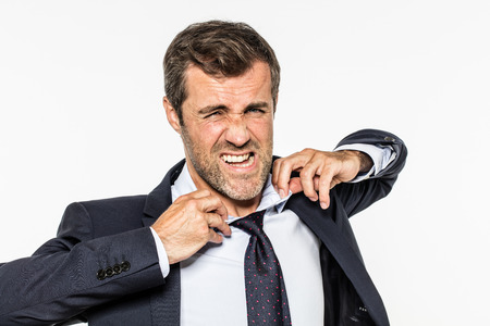 revulsion: revolted bearded businessman suffering from corporate exasperation, tearing his shirt, collar and tie out from management fatigue, white background