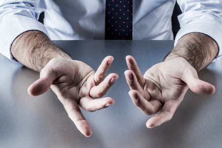 openness: anonymous businessman, salesman or politician hands communicating and discussing with openness with palms and fingers opened, explaining or bargaining at a company Stock Photo