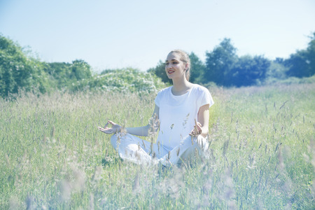 lotus effect: smiling beautiful yoga girl meditating, seated in lotus pose for openness, mindfulness and retreat exercises in green environment, soft romantic filter