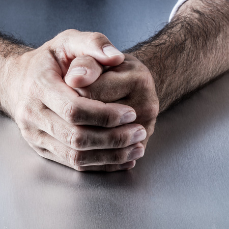 selfcontrol: closeup of anonymous relaxed male hairy hands holding together on a desk expressing reflection, patience or self-control at work