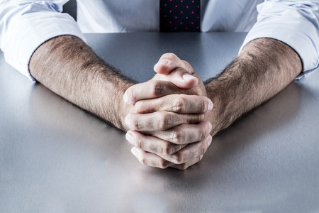 restraint: anonymous leader or politician hands holding tight waiting or thinking at a meeting or interview, communicating about self-control or patience for executive career