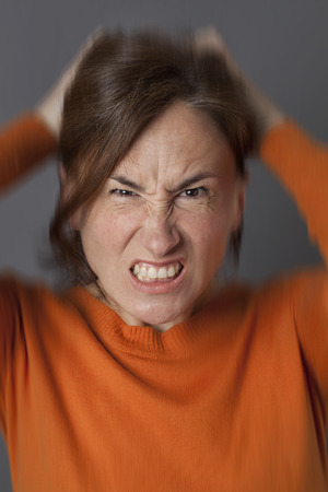 furious middle aged woman pulling out her hair, losing temper, expressing irritation, frustration and stress, blurred effects over grey background