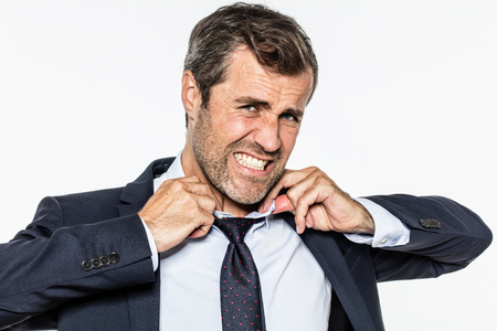 angry bearded businessman in pain, seeking for fresh air, annoyed by corporate pressure, tearing his shirt, collar and tie out for management stress, white background