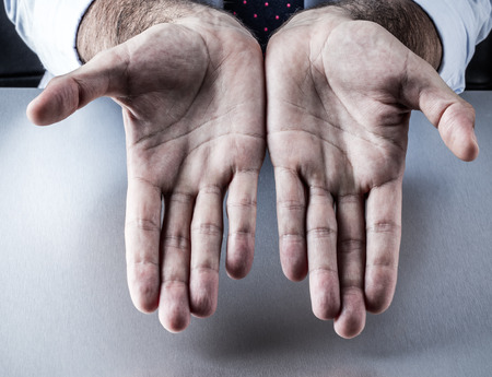 generosity: anonymous businessman with a tie showing his empty hands with palms opened for symbol of generosity, bargain, gift or presentation at the workplace