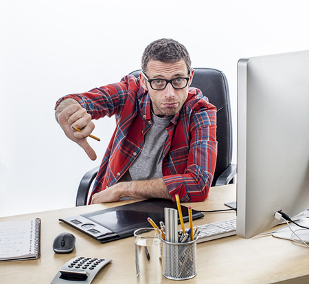 unhappiness: disappointed casual entrepreneur with eyeglasses showing his disillusion with thumbs down, expressing unhappiness and disagreement, white background