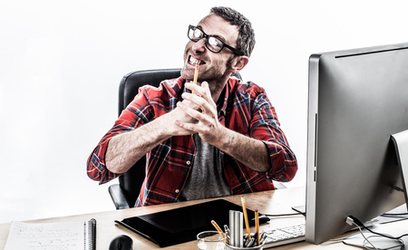 punched out: nervous casual businessman with eyeglasses expressing his irritation and violence with frustrated hands and teeth grinding at his office, contrast effects