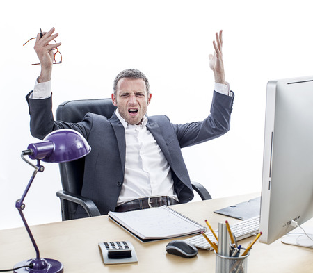 exasperation: complaining middle aged businessman sitting at his office, raising annoyed hands for exasperation, misunderstanding and frustration, isolated, white background