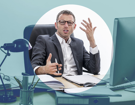 misunderstanding: unhappy frowning middle aged businessman sitting at his desk, expressing misunderstanding, complain and anger, focusing effects Stock Photo