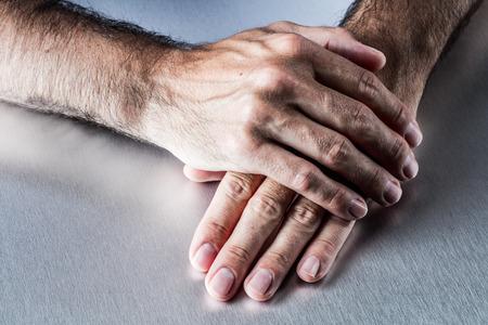 anoniem mannelijke harige handen ontspannen op elkaar plat te wachten of het luisteren, uit te leggen en communiceren over matiging of geduld in lichaamstaal Stockfoto
