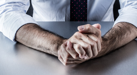 aggressiveness: middle aged businessman hands held firmly showing anger, stress or aggressiveness for body language in office meeting Stock Photo