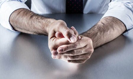 embarrassment: closeup of bothered businessman hands holding fingers with tension expressing controlled exasperation, embarrassment and frustration from management on the workplace Stock Photo