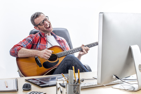 relaxed middle aged entrepreneur singing and playing guitar at his home-office desk to seek for inspiration and wellbeing for his start-up business, white background Stock Photo