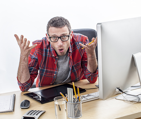 misunderstanding: annoyed casual business man with eyeglasses complaining at his desk, expressing surprise and misunderstanding, white background