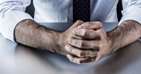 restrained: stubborn businessman hands and fists held firmly showing restrained anger, stress or aggressiveness for fighting body language in corporate business