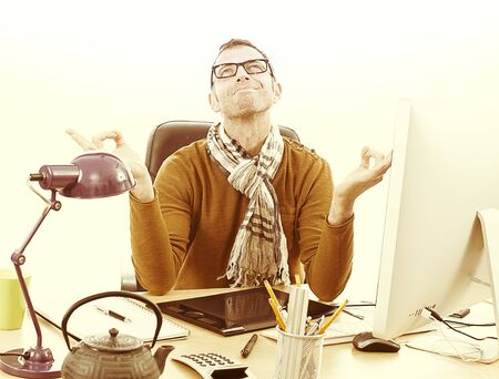 office time: smiling zen casual entrepreneur meditating with relaxing hands at his desk with computer and tea at the office for business reflection, vintage effects