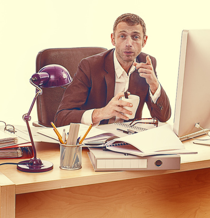 long hours: tired middle aged businessman working late on files and projects at his desk, drinking coffee, pointing his finger to express his unhappiness at long hours, vintage light effects