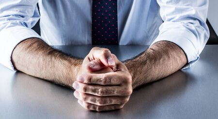 restrained: concept of restrained impatience and business self-control with hands of middle aged corporate man with a tie waiting at meeting or the office Stock Photo